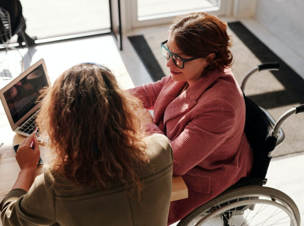 Photo of two women sitting at a desk and looking at a laptop