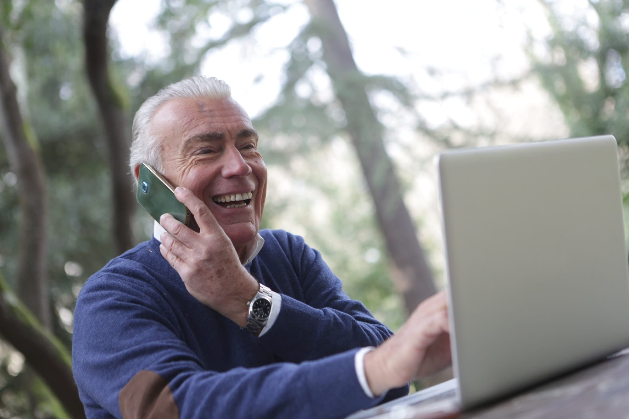 Photo of an elderly man on the phone and on his computer, smiling