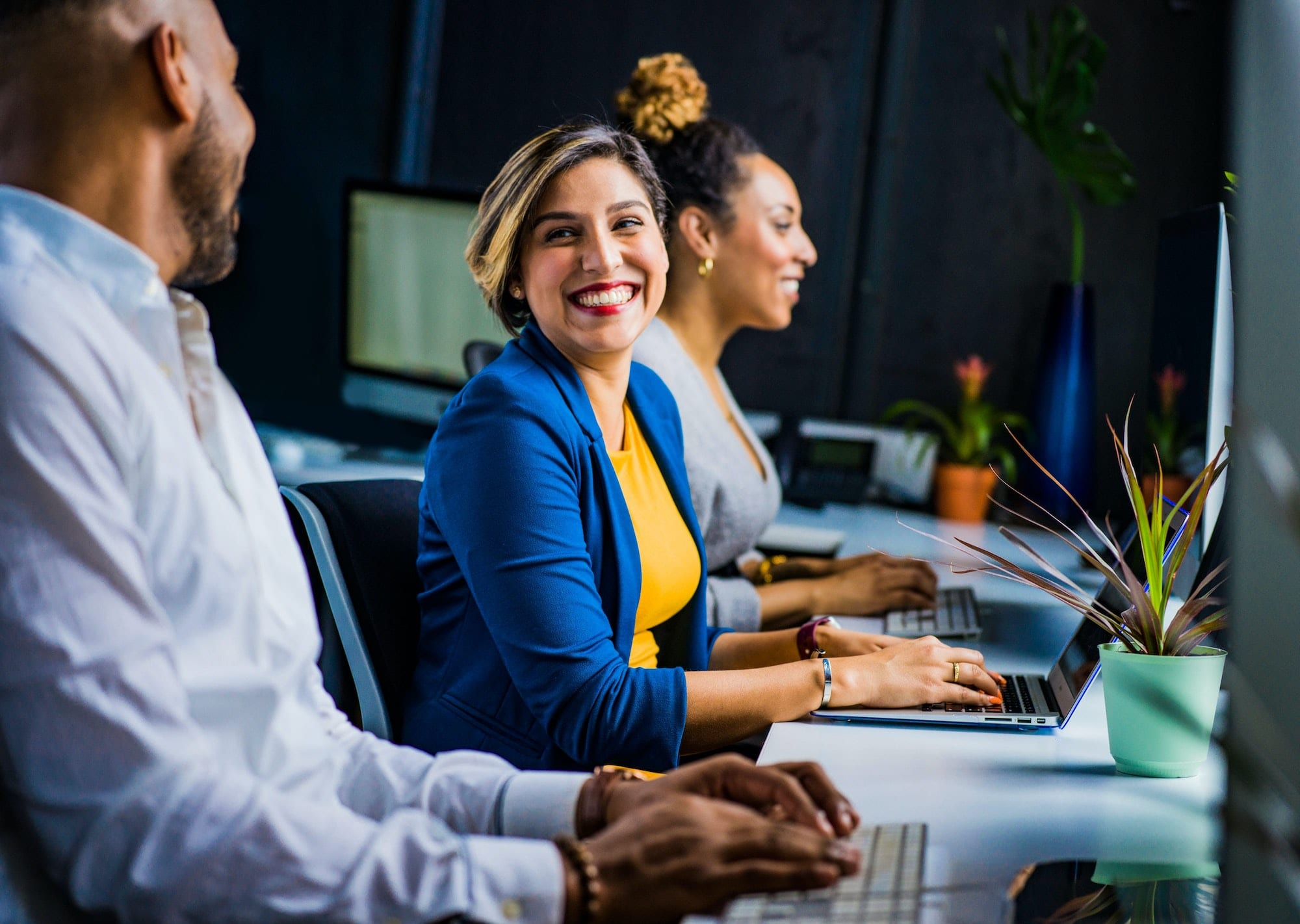 Photo of a woman sitting in front of a computer and smiling at her coworkers
