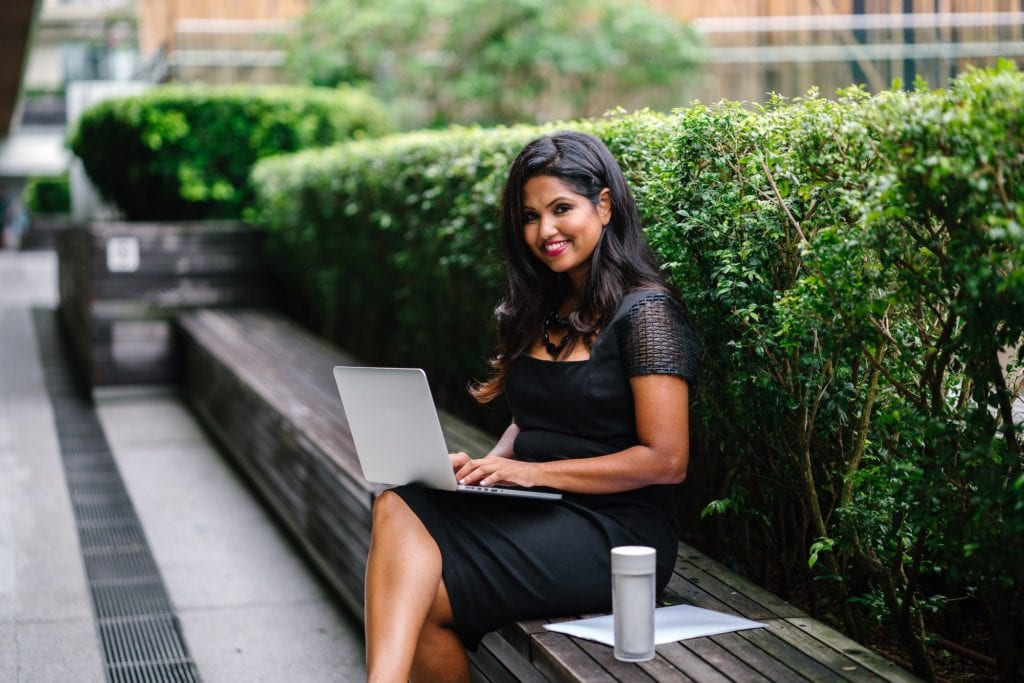 Photo of a young businesswoman sitting on a bench with her laptop