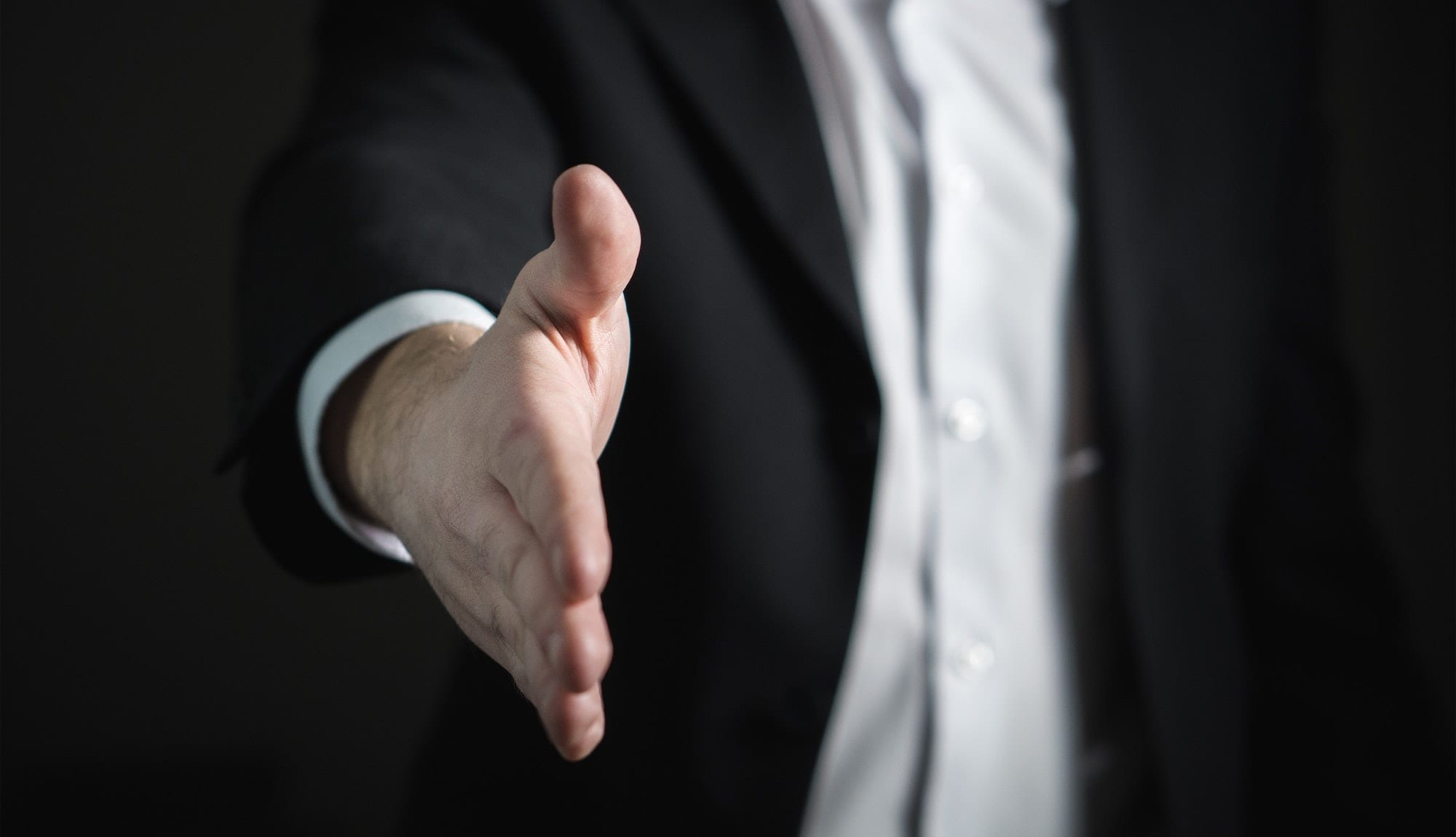 Photo of a man with an outstretched hand like he is going to give someone a handshake