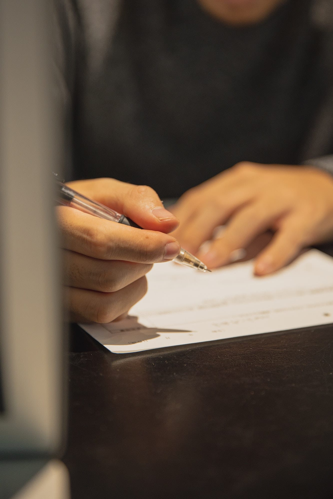 Photo of a person writing on a piece of paper